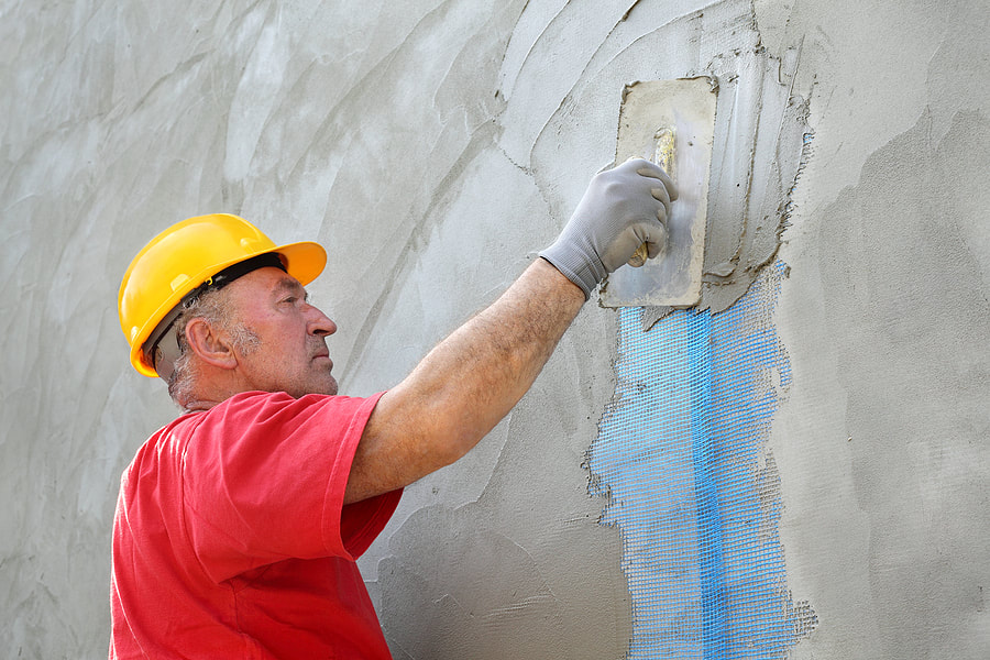 man putting cement on the wall