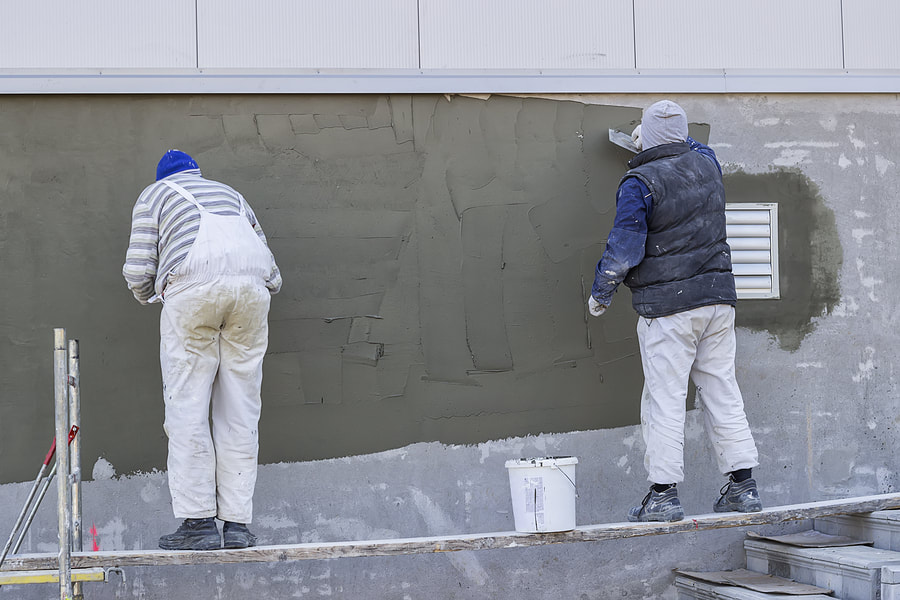 men putting cement to the wall